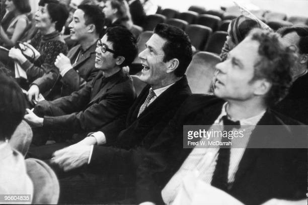American composer John Cage and his partner dancer and choreographer Merce Cunningham watch as paper planes fly overhead at a Fluxus event New York...