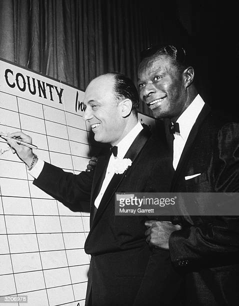 American composer Johnny Green and American pop singer Nat King Cole smile as they stand by the guest board for director Edward Dmytryk's film,...