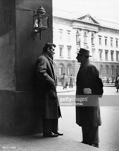 American composer pianist and conductor Leonard Bernstein chatting with a man under the arcarde of piazza della Scala Milan 1955