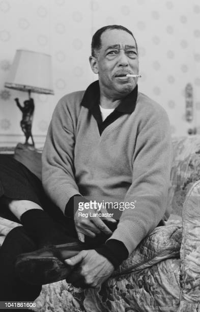 American composer, pianist and jazz musician Duke Ellington pictured smoking a cigarette in a hotel in London on 12th January 1963.