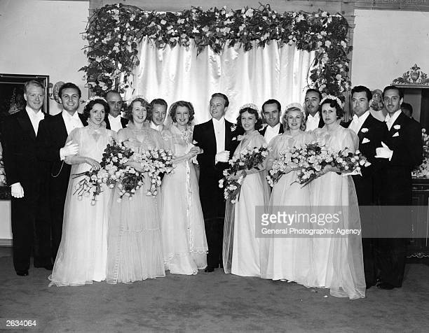 American concert singer and actress Jeanette Macdonald poses with her husband Gene Raymond for a group wedding portrait Many Hollywood celebrities...