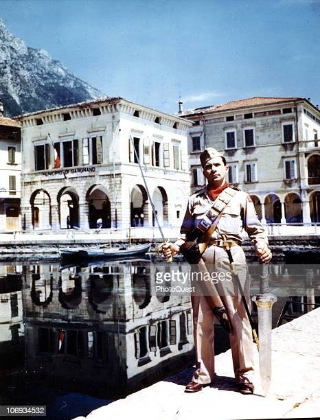 American Corporal Joseph Fileccia poses with two swords taken from a villa named Palazzo Feltrinelli on Lake Garda Gargnano Italy May 1945 Fascist...