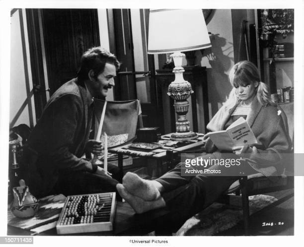 American correspondent Hal Holbrook finds Goldie Hawn reading Russian soldier's manual in a scene from the film 'The Girl From Petrovka' 1974