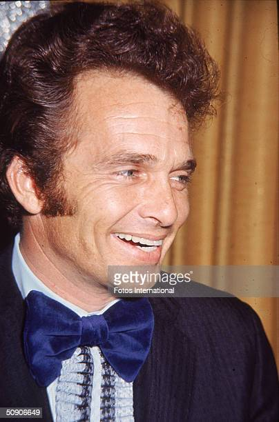 American country and western music star Merle Haggard laughs in front of a gold curtain 1970s