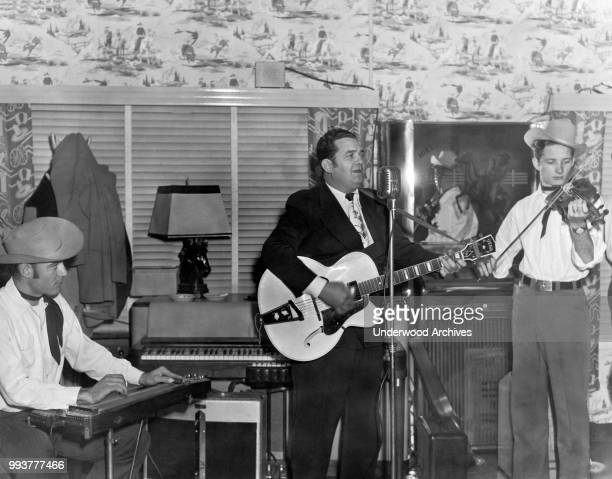 American Country and Western Swing musician Bob Wills plays guitar with his group, the Texas Playboys, Texas, circa 1950. The two men with him are...