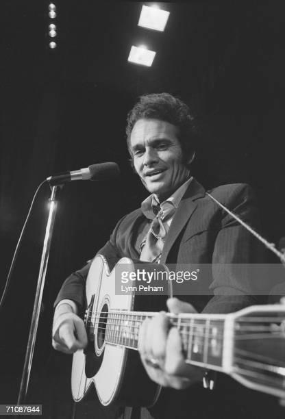 American country music performer Merle Haggard smiles as he plays an acoustic guitar 1970