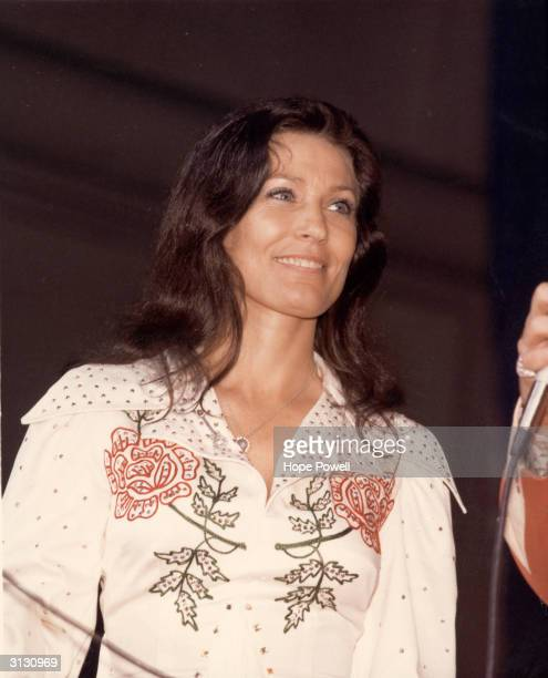 American country music singer and guitarist Loretta Lynn smiles as she looks at an unidentified person offcamera who holds a microphone late 1970s