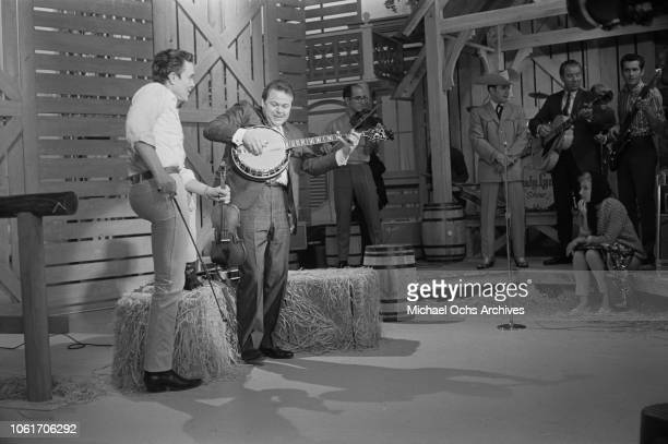 American country music singer and television host Jimmy Dean with guest musician Roy Clark on the set of 'The Jimmy Dean Show' USA 13th November 1964