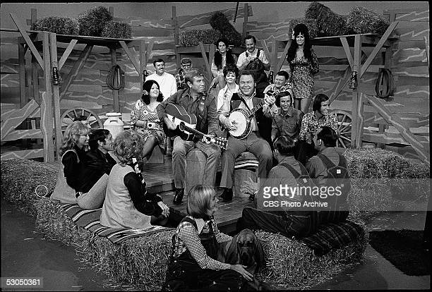 American country music singers Buck Owens and Roy Clark perform a song in front of other cast members on the set of the television variety program...