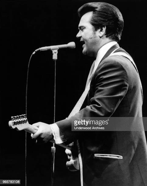American Country musician Conway Twitty plays guitar as he performs onstage at Madison Square Garden, New York, New York, June 3, 1972.