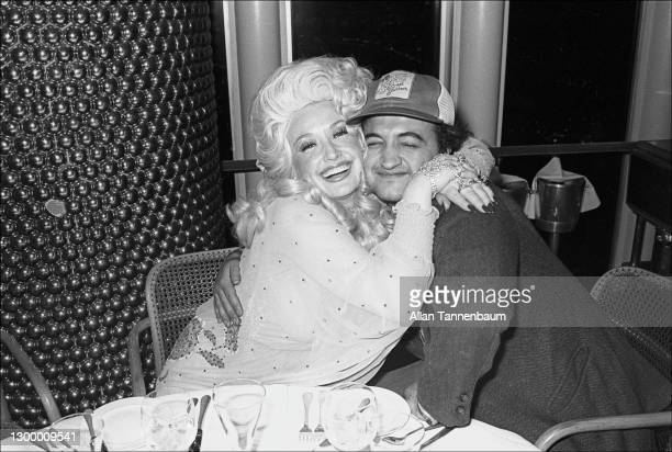 American Country musician Dolly Parton and comedian John Belushi hug as they pose together at the Windows on the World restaurant , New York, New...