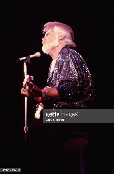 American Country musician Kenny Rogers plays guitar as he performs onstage at Nassau Coliseum, Uniondale, New York, August 29, 1985.