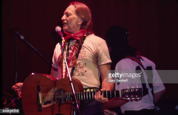 American Country musician Willie Nelson plays guitar as he leads his band, the Family, during a performance at the Palladium, New York, New York,...