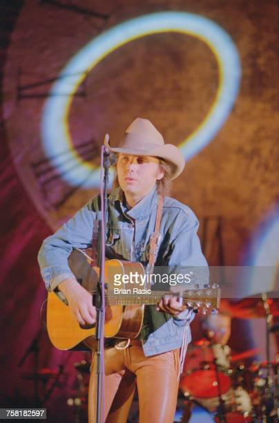 American country singer and musician Dwight Yoakam performs with acoustic guitar live on stage in London in June 1994