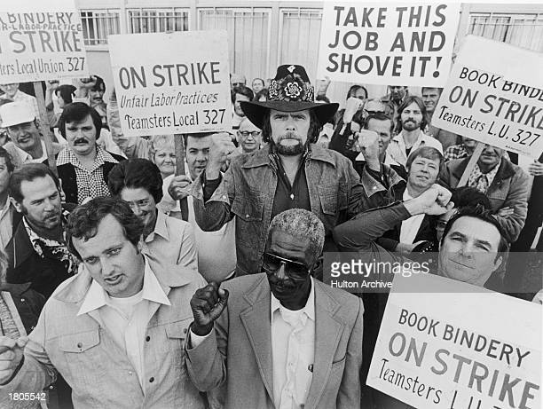 American country singer and songwriter Johnny Paycheck holds a teamsters union sign while joining a group of striking bookbinders 1977