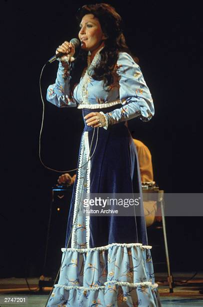 American country singer and songwriter Loretta Lynn performs on stage wearing a long dress circa 1980