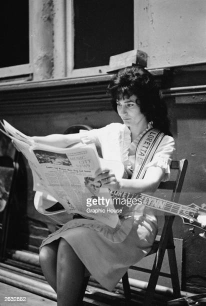 American country singer and songwriter Loretta Lynn reads a newspaper backstage at the Grand Ole Opry Nashville Tennessee early 1960s