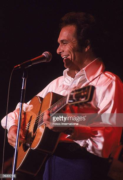 American country singer and songwriter Merle Haggard performs on stage with an acoustic guitar 1970s