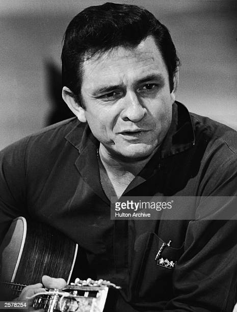American country singer Johnny Cash plays acoustic guitar in a still form his television series, 'The Johnny Cash Show,' circa 1969.