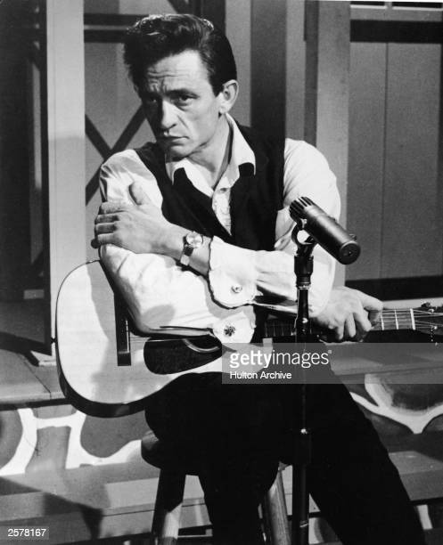 American country singer Johnny Cash sits with an acoustic guitar in a still from the film 'Road To Nashville' directed by Will Zenz 1966