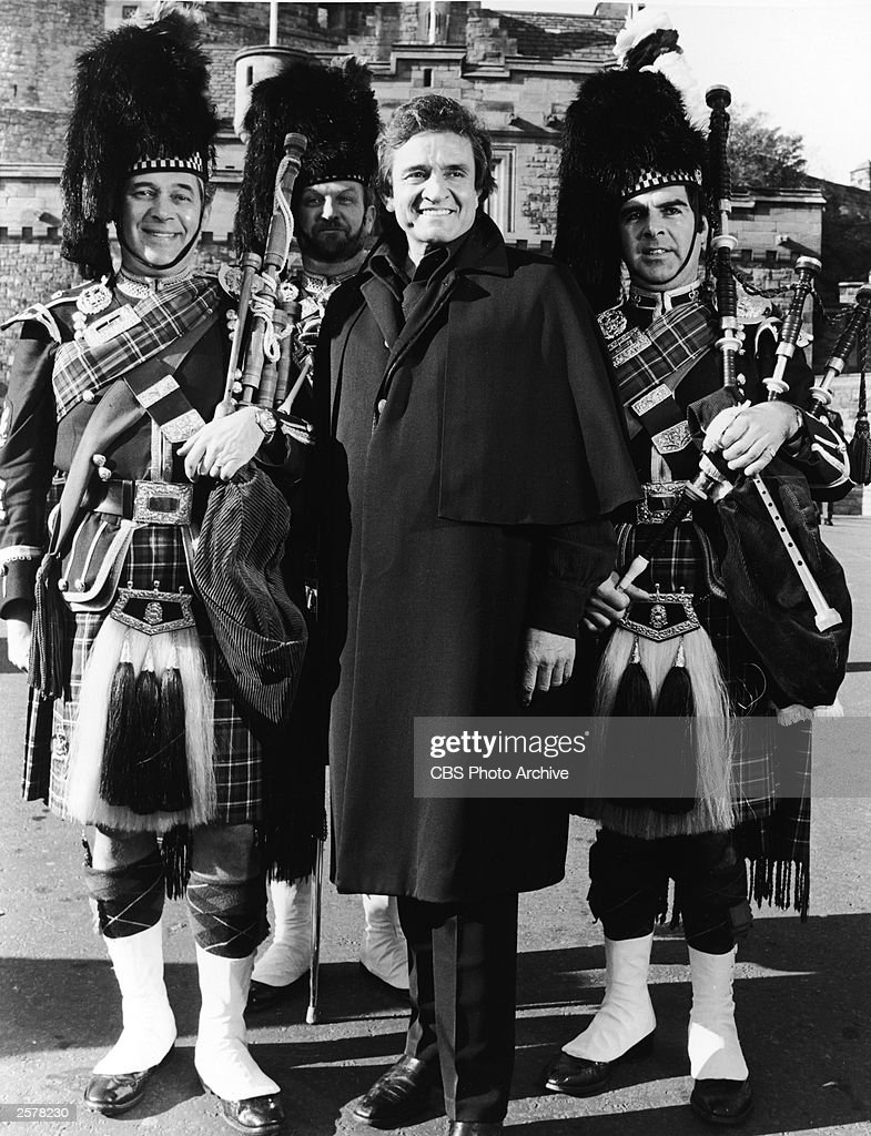 American country singer Johnny Cash (1932 - 2003) smiles as he poses outdoors with three Scottish bagpipers in traditional dress, in a promotional still for his television special, 'Johnny Cash: Christmas in Scotland,' November 13, 1981.