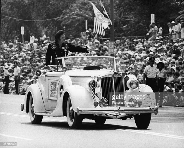 American country singer Johnny Cash waves as he stands in the back of a vintage 1936 Packard convertible Cash served as Grand Marshal of the Grand...