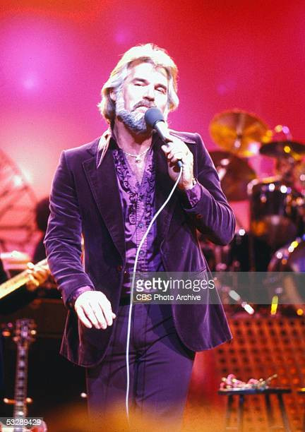 American country singer Kenny Rogers wears a purple velvet suit and ruffled shirt as he performs during the CBS television special 'The Kenny Rogers...