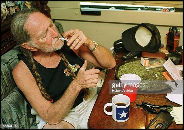 American country singer Willie Nelson takes a drag off a joint while relaxing at his home in Texas 2000s A large amount of marijuana is spread out on...
