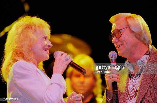 American country singers Tammy Wynette and George Jones perform live on stage together at Hammersmith Apollo in London in September 1995