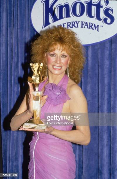 American Country Western music performer Dottie West holds the ACM Award trophy given to the madefortelevision movie 'Elvis' as she attends the...