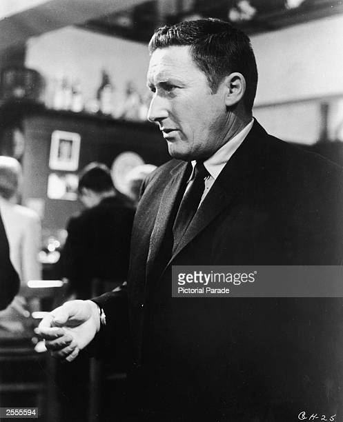 American crime writer Mickey Spillane stands looking to the side in a bar circa 1960