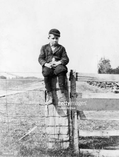 American criminal and future FBI 'public enemy number one' John Dillinger as a young boy seated on a fence post on his father's Indiana farm