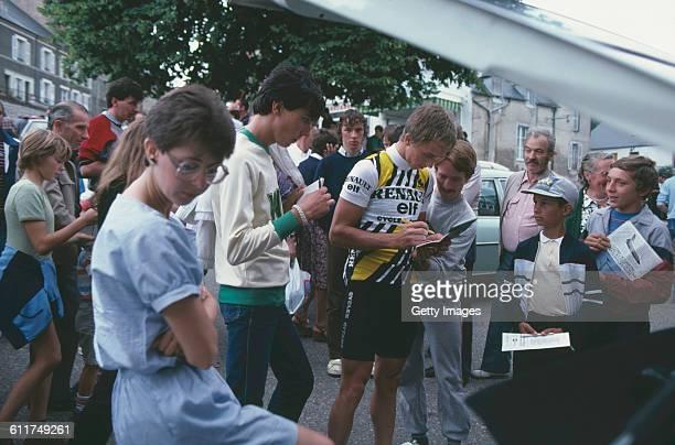American cyclist Greg LeMond signs autographs at the Critérium de Château-Chinon road race, Château-Chinon, Nièvre, France, circa 1982.