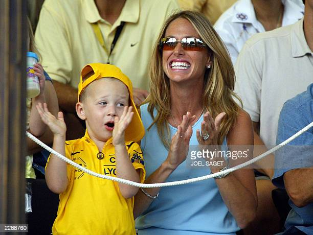 American cyclist Lance Armstrong's son Luke and his wife Kristin applaud at the end of the 20th and last stage of the 90th Tour de France cycling...