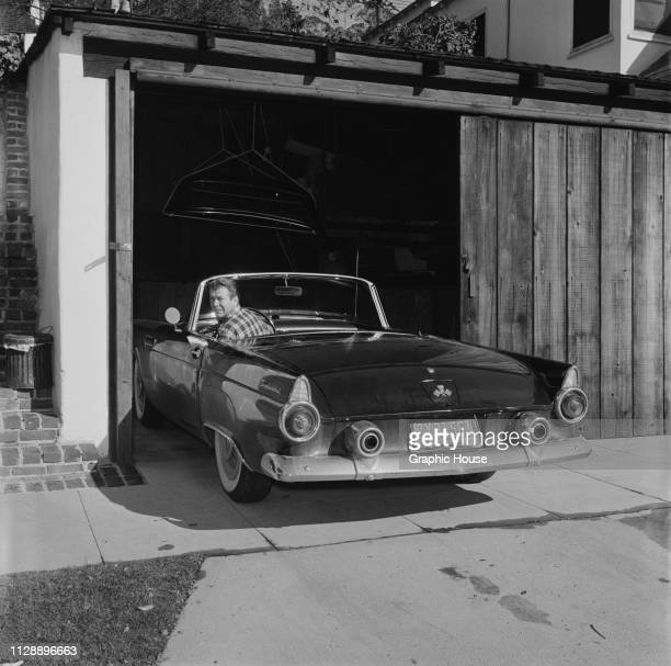 American dancer actor screenwriter and director Gene Nelson sitting in the driver seat of his Ford Thunderbird at home California US 21st December...