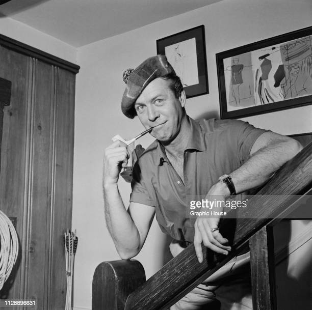 American dancer actor screenwriter and director Gene Nelson smoking a pipe at home California US 21st December 1955