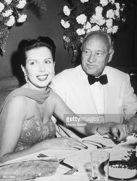 American dancer and actor Ann Miller smiles while sitting in a booth with American hotelier Conrad Hilton at a Damon Runyon Cancer Fund benefit at...