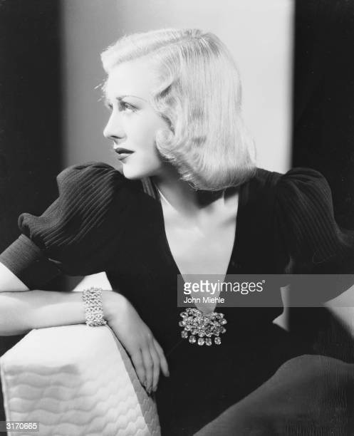 American dancer and actress Ginger Rogers wearing a low cut evening dress with a large jewelled brooch.