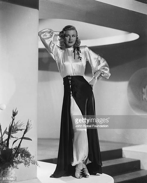 American dancer and actress Ginger Rogers wearing a silky white gown with a dark wraparound skirt over the top.