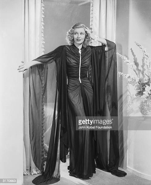 American dancer and actress Ginger Rogers wearing a striking filmy evening gown with a ruche front and flowing sleeves