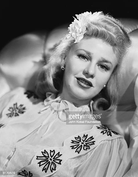 American dancer and actress Ginger Rogers wearing a white blouse with a floral motif and a flower in her hair for her role as Jo Jones in 'Tender...