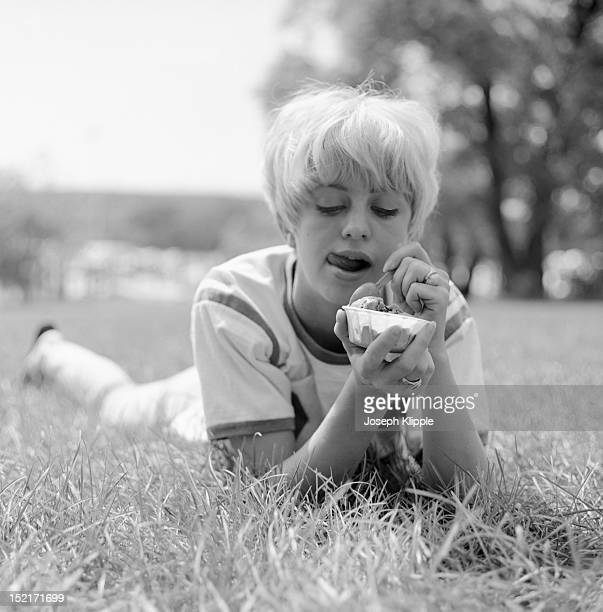 American dancer and dance instructor, and future actress, Goldie Hawn, dressed om a football jersey, lies on the grass and eats ice cream, Washington...