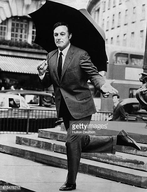American dancer and film actor Gene Kelly dancing in the rain at Piccadilly Circus London 1970