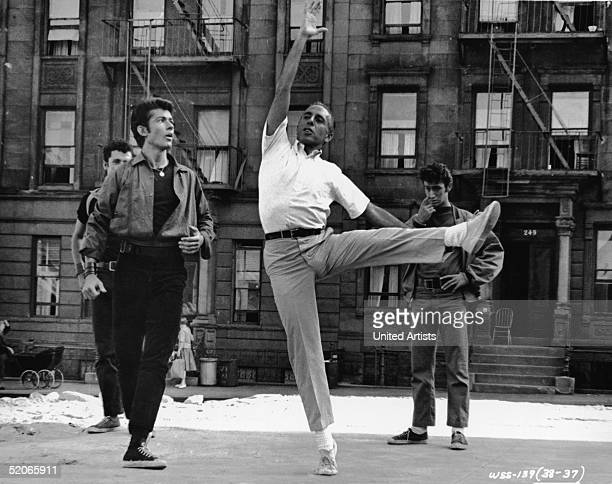American dancer choreographer and director Jerome Robbins demonstrates a dance move to American actor George Chakiris during the filming of 'West...