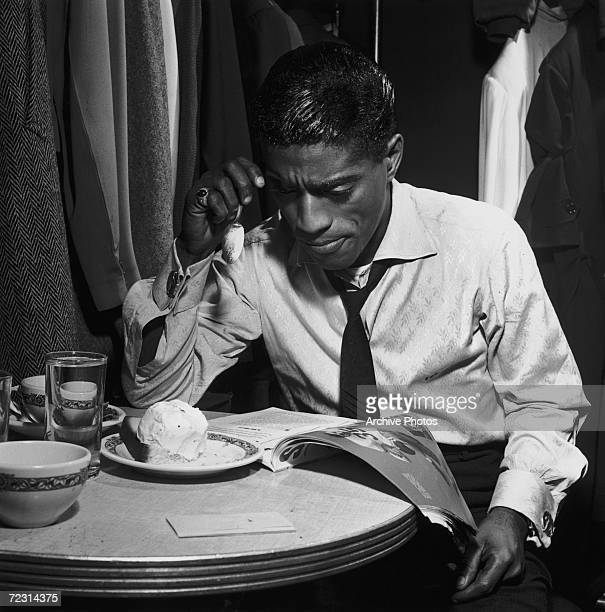American dancer singer and actor Sammy Davis Jr eats pound cake a la mode whilst reading a magazine in his dressing room 4th November 1953