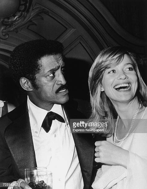 American dancer singer and actor Sammy Davis Jr stands next to British actress Judy Geeson at a party October 1976 Davis is wearing a tuxedo with a...