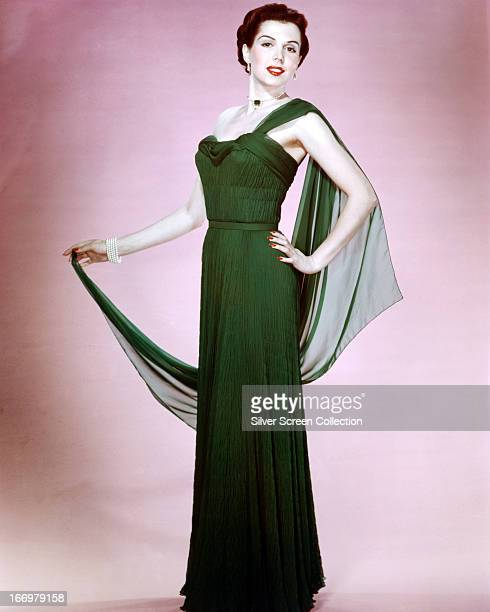 American dancer singer and actress Ann Miller wearing a full length offtheshoulder dress in green ruched fabric circa 1945
