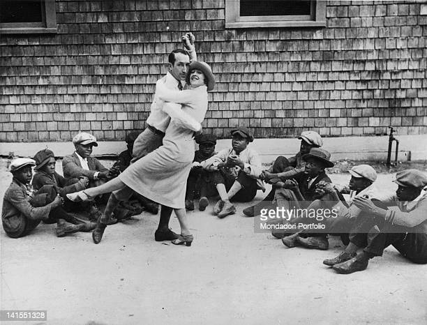 American dancers Marion and Martinez Randall performing a charleston step watched by some black children sitting on the ground Palm Beach 1920s
