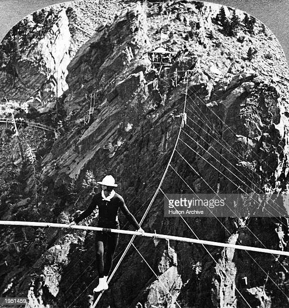 American daredevil and aviator William 'Ivy' Baldwin balances himself with a pole while crossing South Boulder Canyon Eldorado Springs Colorado July...