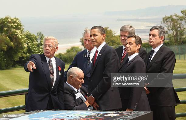 American D-Day veterans Clyde Combs and Ben Franklin point to Omaha beach as they talk with Prince Charles, The Prince of Wales, U.S. President...